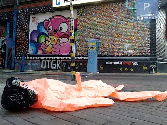 Street Art in Amsterdam: Inflatable Doll in front of the art work of Ottograph.